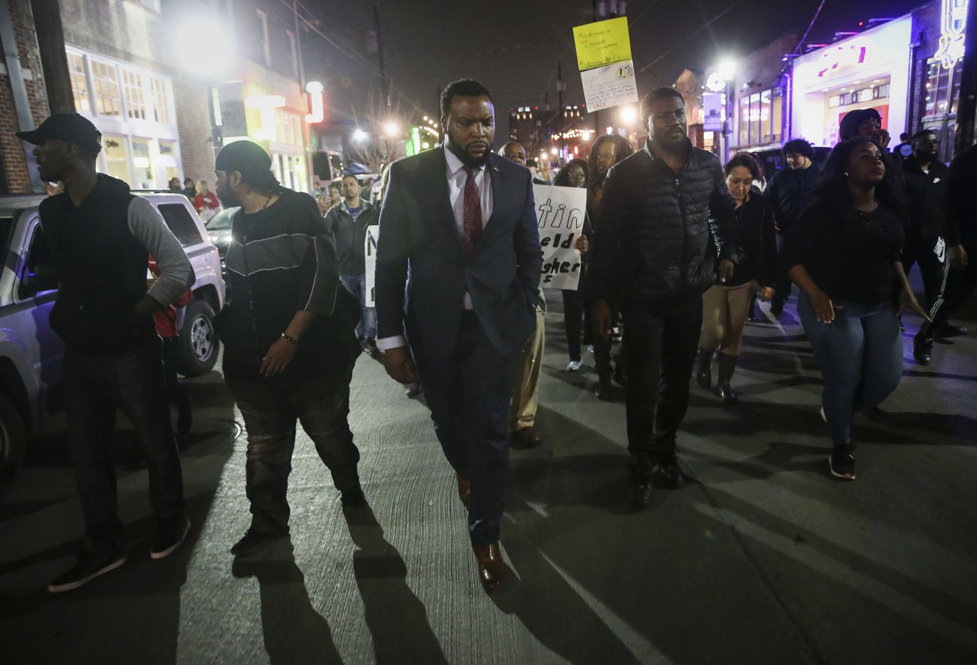 Attorney Lee Merritt, center with dress tie, joins demonstrators march through the street during a protest Saturday, March 23, 2019 in Dallas' Deep Ellum neighborhood. Civil rights activists are calling for felony charges, including hate-crimes charges, to be filed against Austin Shuffield, 30, who currently faces misdemeanor charges of assault causing bodily injury and interfering with an emergency call in connection with a violent attack Thursday morning that began with a parking dispute and escalated into a physical confrontation. A lawyer for the unidentified 24-year-old woman said Shuffield berated the woman with racial slurs.