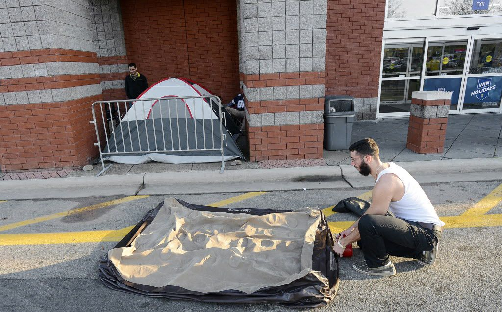 Noor Mansoor takes down the air mattress from his tent before entering as the first person for holiday shopping at Best Buy, Thursday, Nov. 26, 2015, in Durham, N.C.