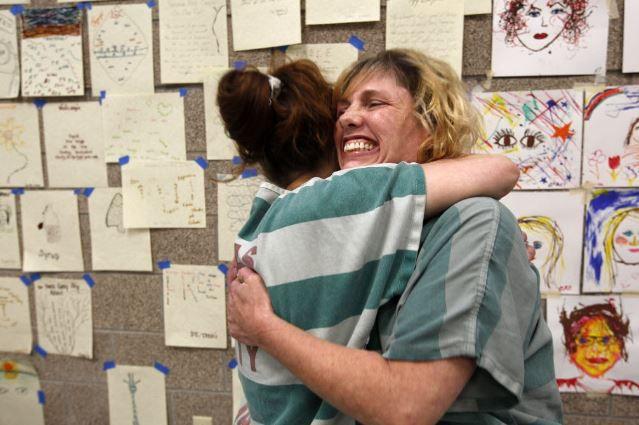 Dallas County prisoners hug during a rehabilitation program.