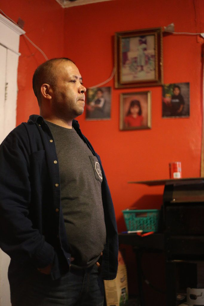 Armando Rivera stands inside his home of 12 years, in Commerce, Texas. Pictures of his children hang on the wall behind him. Rivera has U.S. citizen children but is fearful of enrolling them in government insurance programs because of his pending immigration case. (Obed Manuel/Staff)