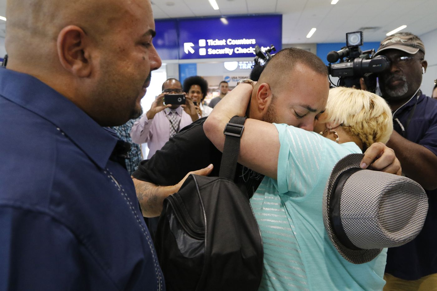 Anthony Wiggs, left and Raymond Ramirez, center, meet their biological mother Elsie Ramirez for the first time. The two were separated from their mother as infants, but a DNA search led them to her 47 years later. They were reunited on Friday, August 4, 2017 at Dallas/Fort Worth International Airport.