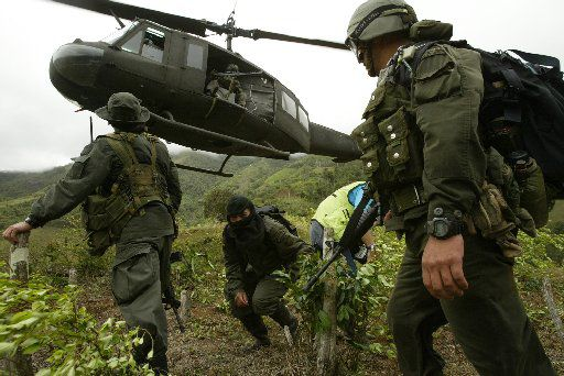 Accompanied by a hooded informant, members of a Colombian police anti-narcotics unit landed in a coca field in the rural area of Cumbitara in southern Colombia in 2004.