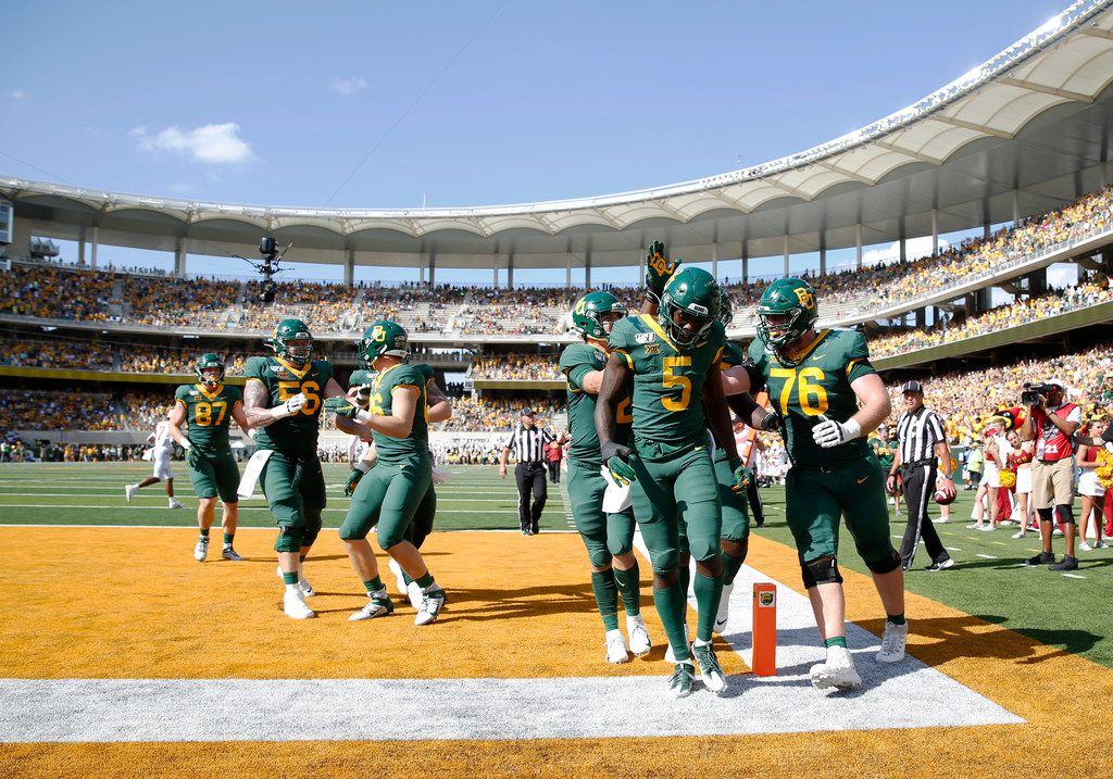 Baylor Bears wide receiver Denzel Mims (5) is congratulated by Baylor Bears quarterback Charlie Brewer (12), Baylor Bears offensive lineman Connor Galvin (76) and Baylor Bears offensive lineman Xavier Newman (55) after scoring the first touchdown of the game in the first half of play at McLane Stadium in Waco, Texas on Saturday, September 28, 2019. Baylor Bears defeated Iowa State Cyclones 23-21. (Vernon Bryant/The Dallas Morning News)