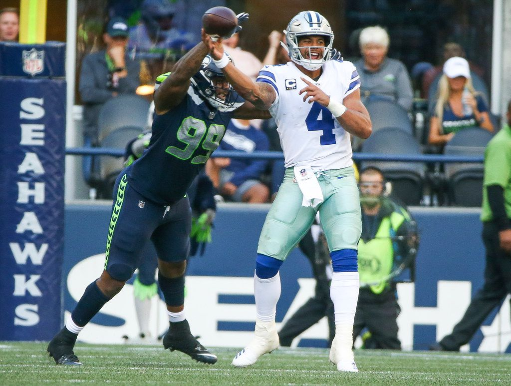 Seattle Seahawks defensive tackle Quinton Jefferson (99) nearly causes Dallas Cowboys quarterback Dak Prescott (4) to fumble the ball during the second half of an NFL game between the Dallas Cowboys and Seattle Seahawks on Sunday, September 23, 2018 at CenturyLink Field in Seattle. (Shaban Athuman/The Dallas Morning News)