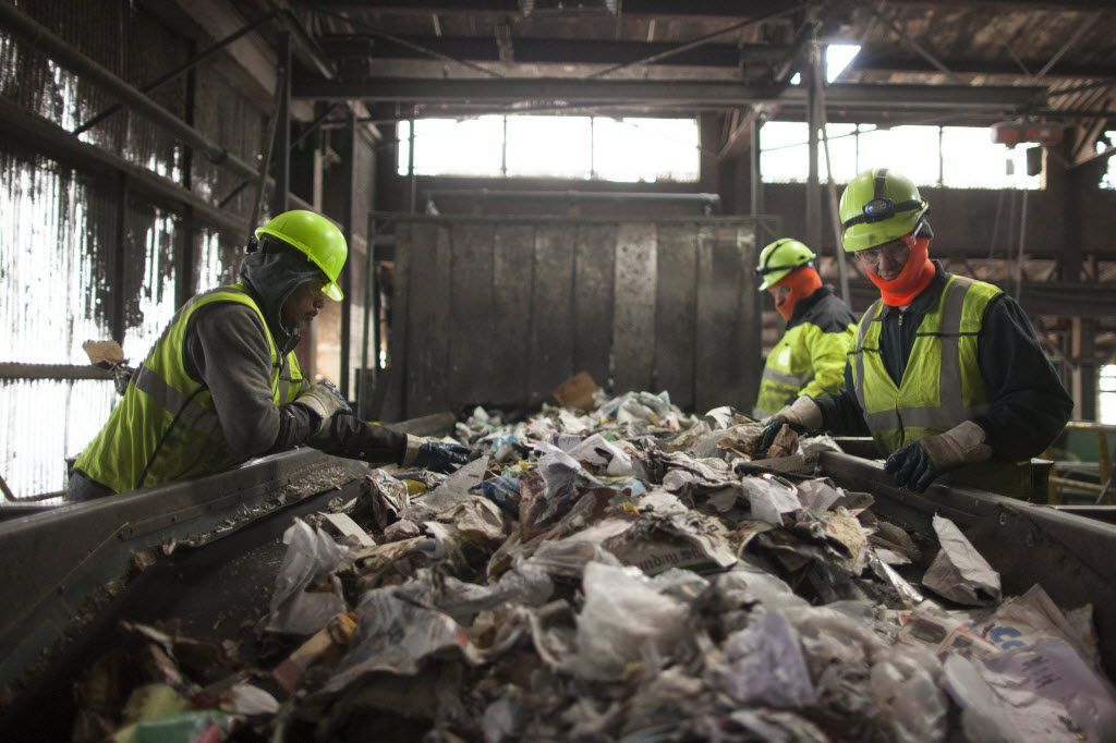 Workers remove contaminants from a stream of recyclables at the Waste Management facility in Newark, N.J. (Dave Sanders/The New York Times)