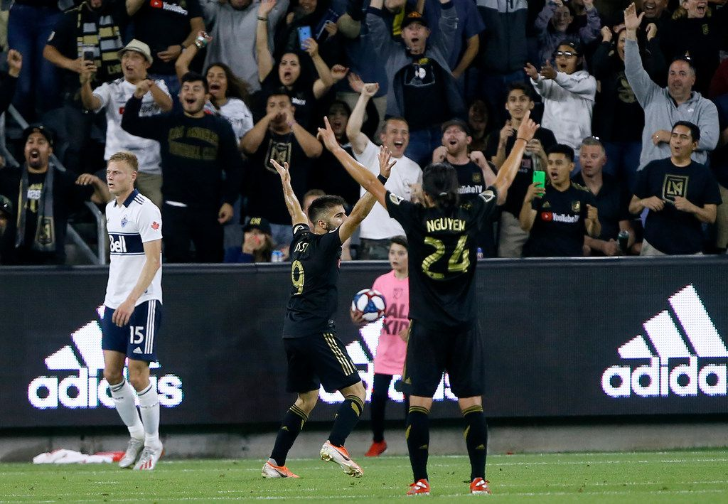 Los Angeles FC forward Diego Rossi (9) celebrates his goal with midfielder Lee Nguyen (24), as Vancouver Whitecaps midfielder Andy Rose (15) looks away during the second half of a Major League Soccer match in Los Angeles, Saturday, July 6, 2019. (AP Photo/Alex Gallardo)