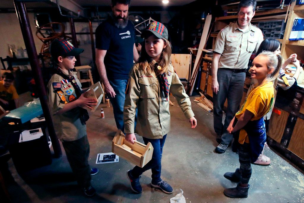 Tatum Weir (center) carries a toolbox she built as her twin brother Ian follows after a Cub Scout meeting in Madbury, N.H. For 108 years, the Boy Scouts of America's flagship program for older boys has been known simply as the Boy Scouts. With girls entering the ranks, the BSA says that will change to Scouts BSA.