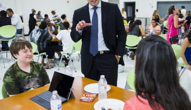 El presidente de la junta escolar de Dallas Miguel Solís habla con un par de alumnos de la nueva Academia de Innovación, Diseño y Empresariado en la preparatoria Fannin. (DMN/ASHLEY LANDIS)