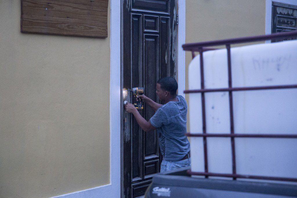 """SAN JUAN, PUERTO RICO - SEPTEMBER 19:  A resident in the La Perla neighborhood in Old San Juan secures a building as residents prepare for a direct hit from Hurricane Maria on September 19, 2017 in San Juan, Puerto Rico. Puerto Rico Gov. Ricardo Rossello is saying Maria could be the """"most catastrophic hurricane to hit"""" the U.S. territory in a century. (Photo by Alex Wroblewski/Getty Images)"""