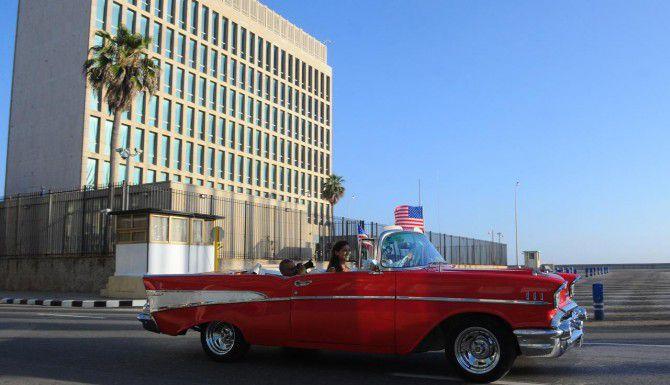 Un carro antiguo pasa al frente de la embajada de Estados Unidos en Cuba. La bandera estadounidense ondea en la sede diplomática de La Habana luego de 54 años años. (AFP/GETTY IMAGES/YAMIL LAGE)