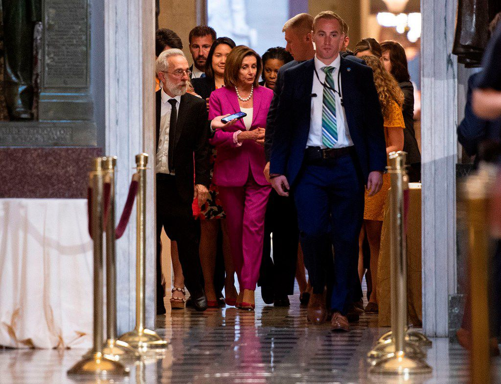"""US speaker of the House, Nancy Pelosi (C) walks with reporters, before the Democrat controlled House of Representatives passed a resolution condemning US President Donald Trump for his """"racist comments"""" about four Democratic congresswomen the day before, at the Capitol in Washington, DC on July 16, 2019."""