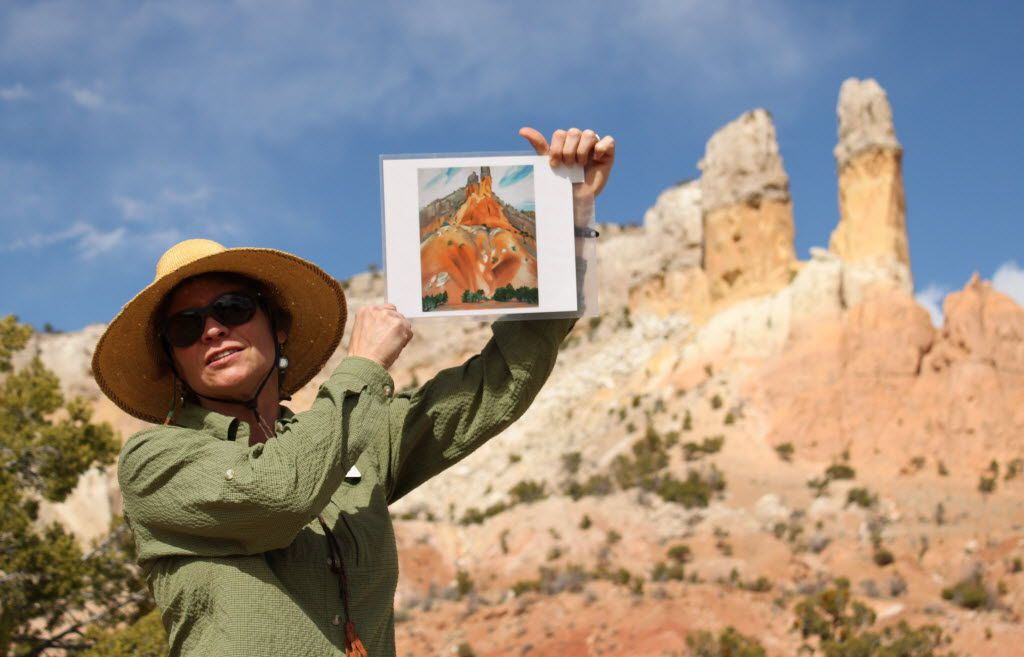 Ghost Ranch tour guide Karen Butts holds up a copy of Georgia O'Keeffe's The Cliff Chimneys, 1938  during a tour of the places the artist painted at Ghost Ranch.
