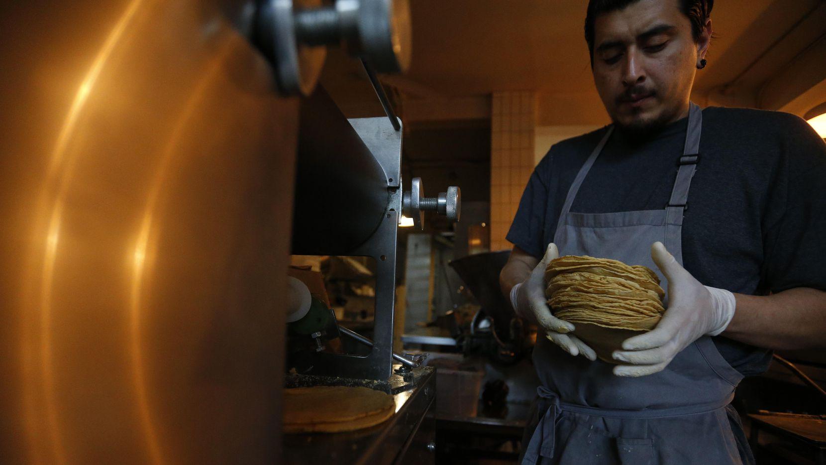 Jesús Saldivar toma tortillas recien salidas de la máquina del Molino El Pujol, en la Ciudad de México. (AP/Rebecca Blackwell)