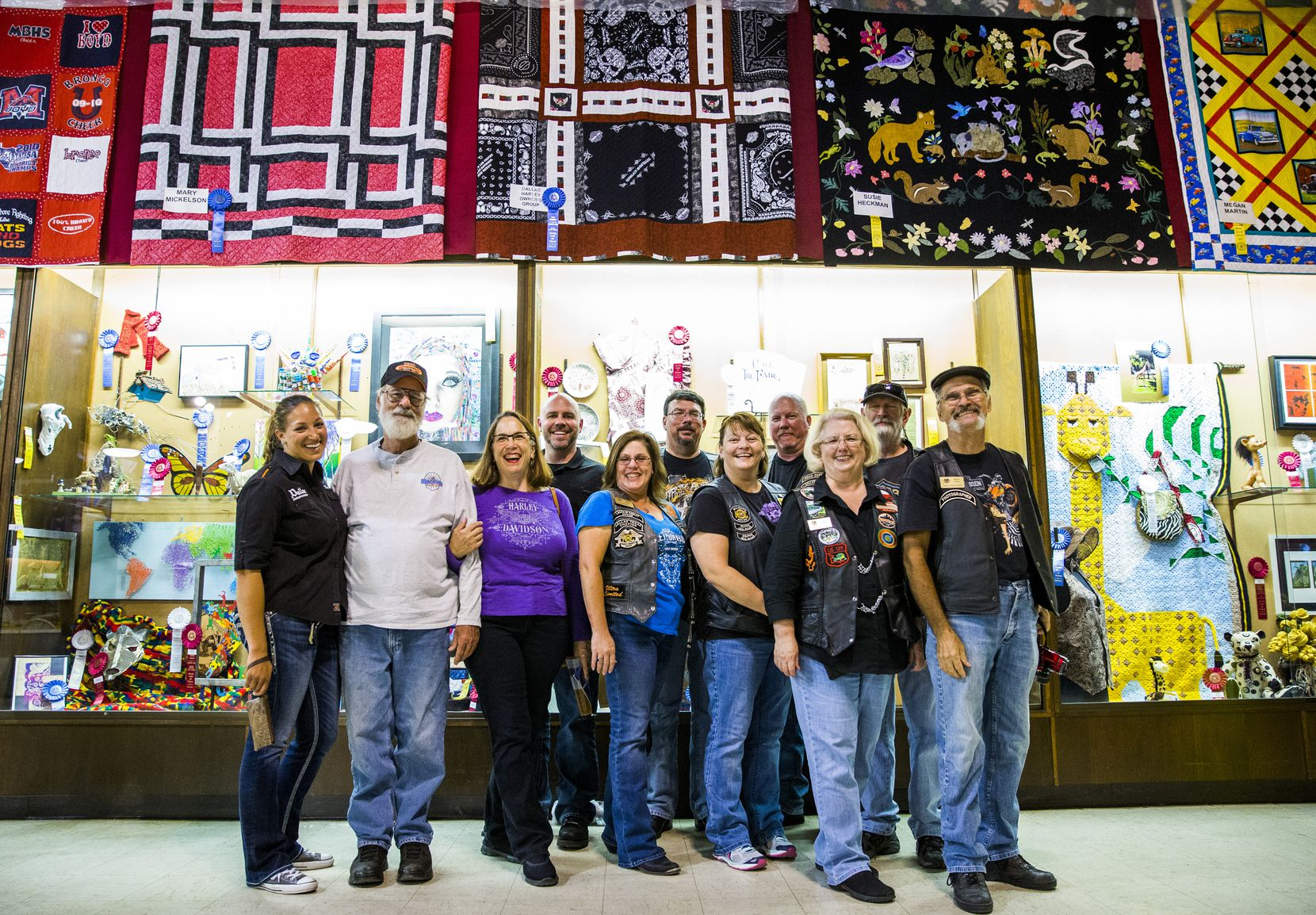 Members of the Dallas Harley Owners Group pose  beneath their prize-winning quilt.  Julie Steger (third from left, in purple), a longtime quilter, coordinated the operation.