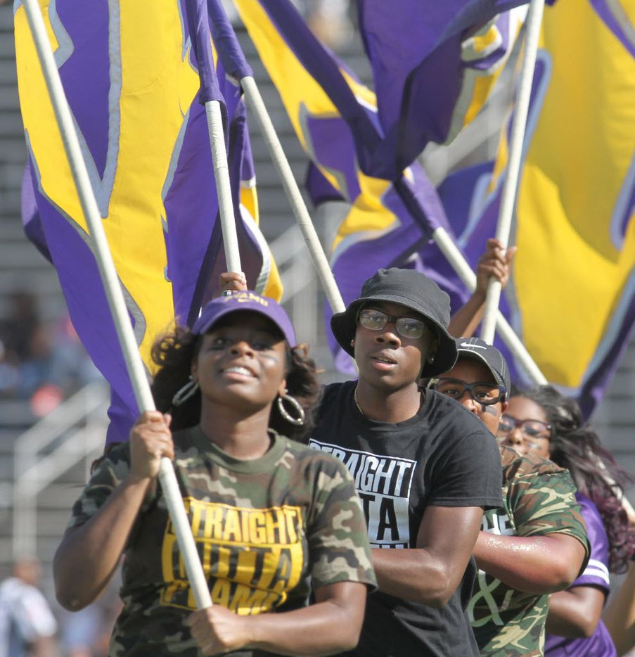 A group of Prairie View A&M fans race across the field waving flags in celebration of a touchdown during the first half against Grambling in 2015.