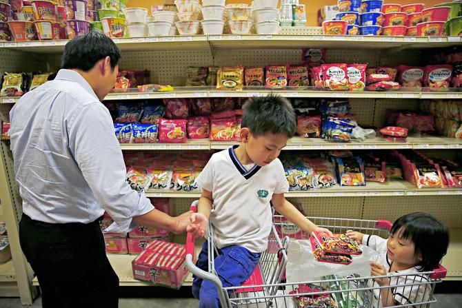 Six-year-old Chester Sheu hands noodles to his 4-year-old sister, Alyssa Sheu, as they help their father, David Sheu, shop at Tian Tian Supermarket in the DFW China Town in Richardson. Sheu emigrated from Taiwan 20 years ago.