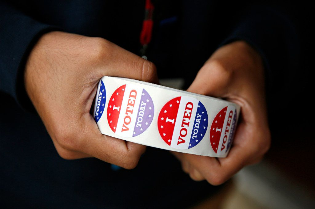 """Norberto Garcia holds a roll of """"I Voted Today"""" stickers outside of a polling place at Vickery Baptist Church on November 8, 2016 in northeast Dallas."""
