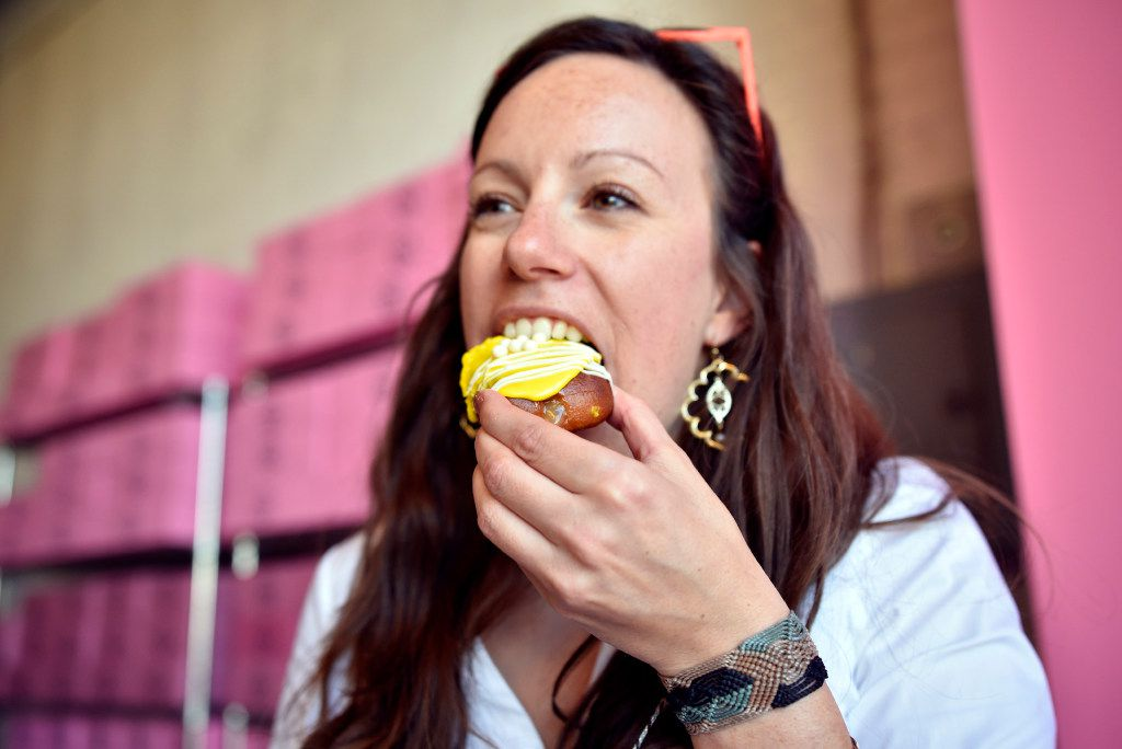 Journalist Tiney Ricciardi takes a bite of a Deep Ellum mother pucker donut during a revealing of the new donuts by Glazed Donut Works in Deep Ellum, on Wednesday, Nov. 16, 2016 in Dallas.