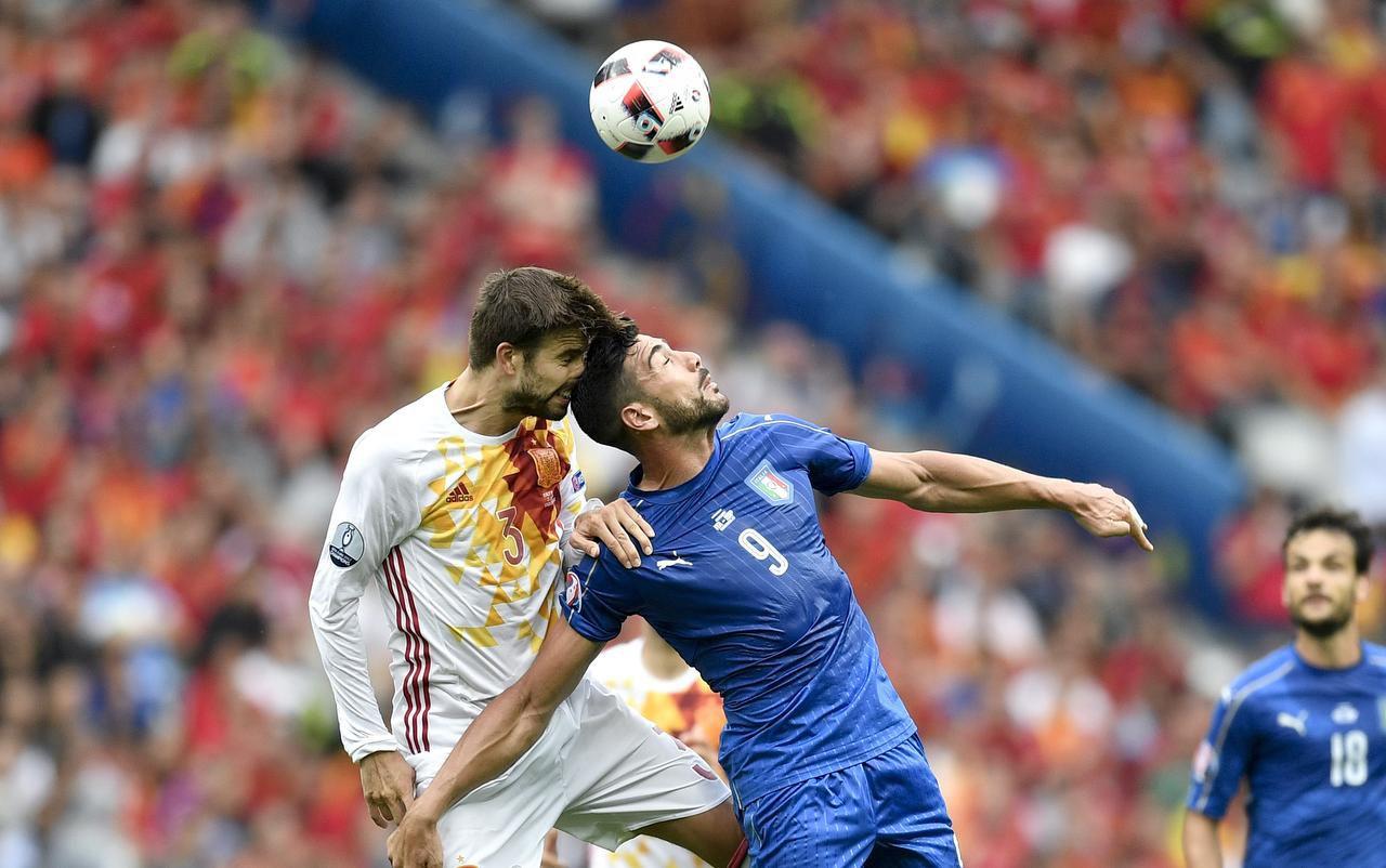 Gerard Pique de España y Graziano pelle de Italia intentan cabecear el balón en el partido de segunda ronda de la Eurocopa. (AP/Martin Meissner)