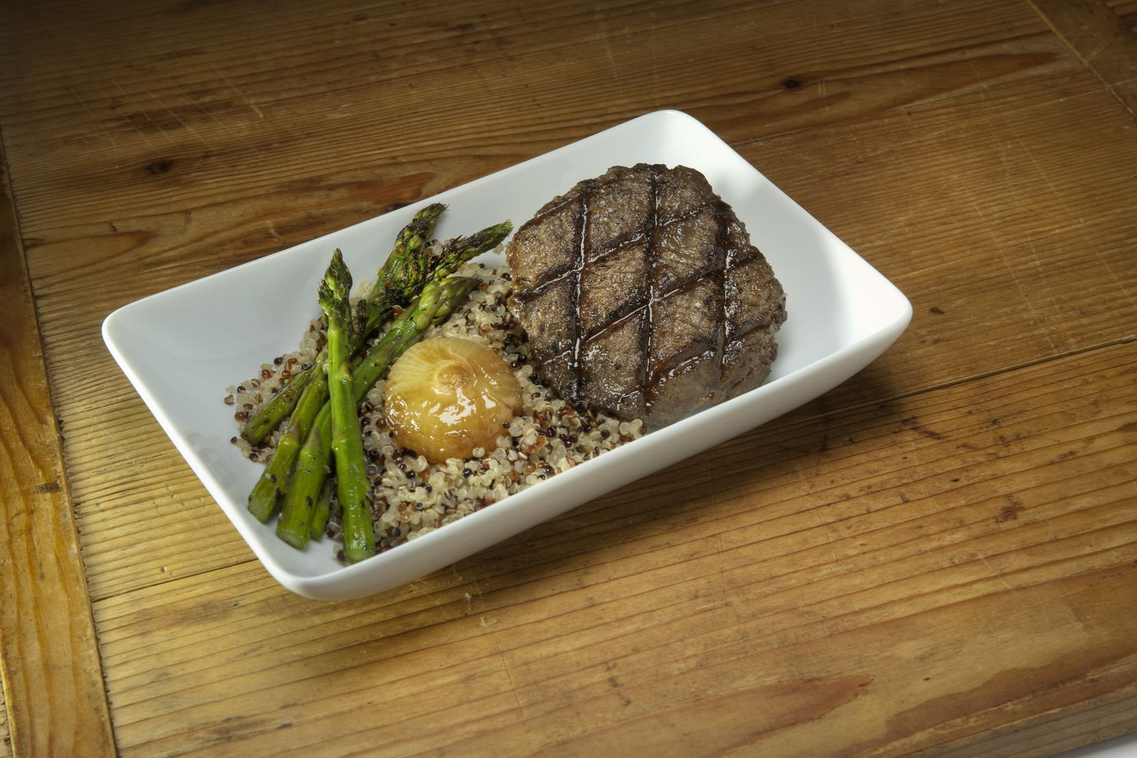 A peppercorn-crusted tenderloin with asparagus and quinoa is one of several dishes designed by Dallas chef Julian Barsotti debuting on American Airlines flights Nov. 1