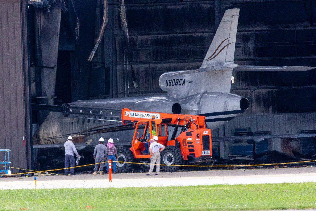 NTSB and others inspect a damaged and burned hangar where a plane crashed a day earlier at Addison Airport in Addison, Texas on Monday, July 1, 2019. The plane, a Beechcraft Super King Air 350, had just taken off when it crashed killing all ten people on board. The plane on the left is not the one that crashed. This plane was already in the hangar. (Shaban Athuman/Staff Photographer)