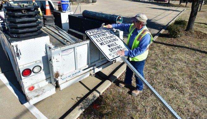 Un trabajador coloca los nuevos señalamientos para recordar a los residentes de Denton que es manejar y textear ya es ilegal en su localidad. (DENTON RECORD-CHRONICLE/DAVID MINTON)