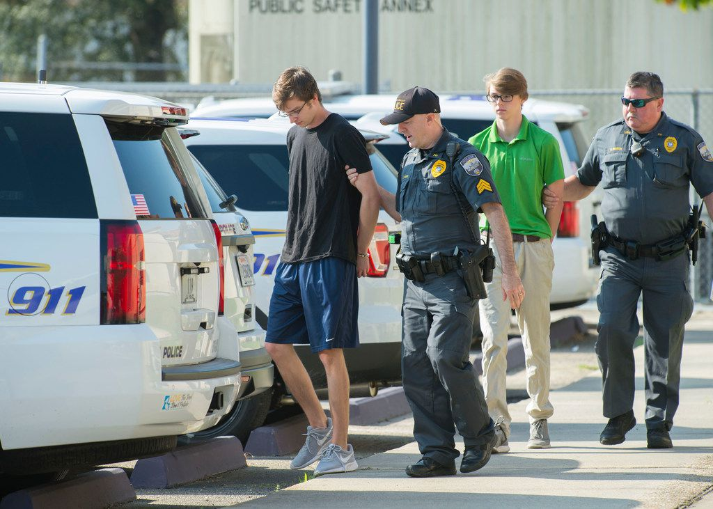 Zachary Hall, left and Sean Pennison, second from right, are escorted by LSU Police officers after being booked at LSU Police Dept. headquarters on charges of hazing on Wednesday, Oct. 11, 2017 in Baton Rouge, La.  Multiple people were arrested Wednesday on hazing charges in the death of Maxwell Gruver, a Louisiana State University fraternity pledge whose blood-alcohol content level was more than six times the legal limit for driving, officials said.  Matthew Alexander Naquin also faces a negligent homicide charge.   (Travis Spradling/The Advocate via AP)
