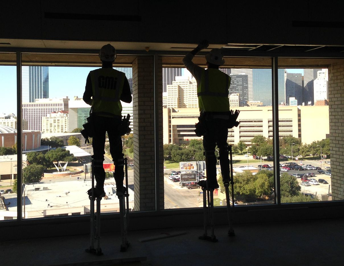 Workers in the top floor ballroom of the Lorenzo Hotel overlooking downtown Dallas.