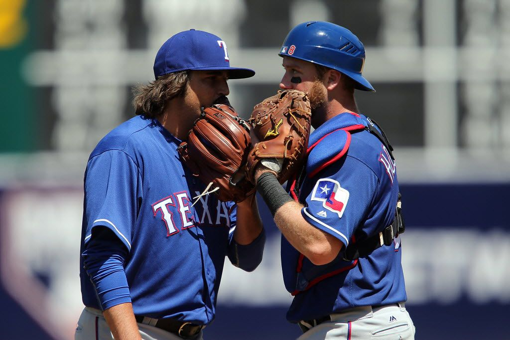 OAKLAND, CA - MAY 18:  Luke Jackson #77 of the Texas Rangers talks with Bryan Holaday #8 of the Texas Rangers in the eighth inning against the Oakland Raiders at Oakland Coliseum on May 18, 2016 in Oakland, California.  (Photo by Don Feria/Getty Images)