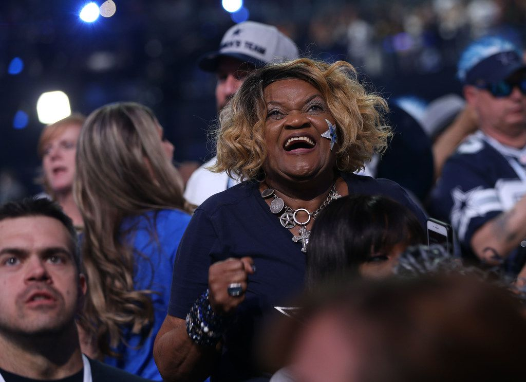 Dallas Cowboys fan Carolyn Price reacts as Dallas Cowboys center Travis Frederick begins to announce the team's third round pick wide receiver Michael Gallup during the 2018 NFL draft at AT&T Stadium in Arlington, Texas on Friday, April 27, 2018. (Rose Baca/The Dallas Morning News)