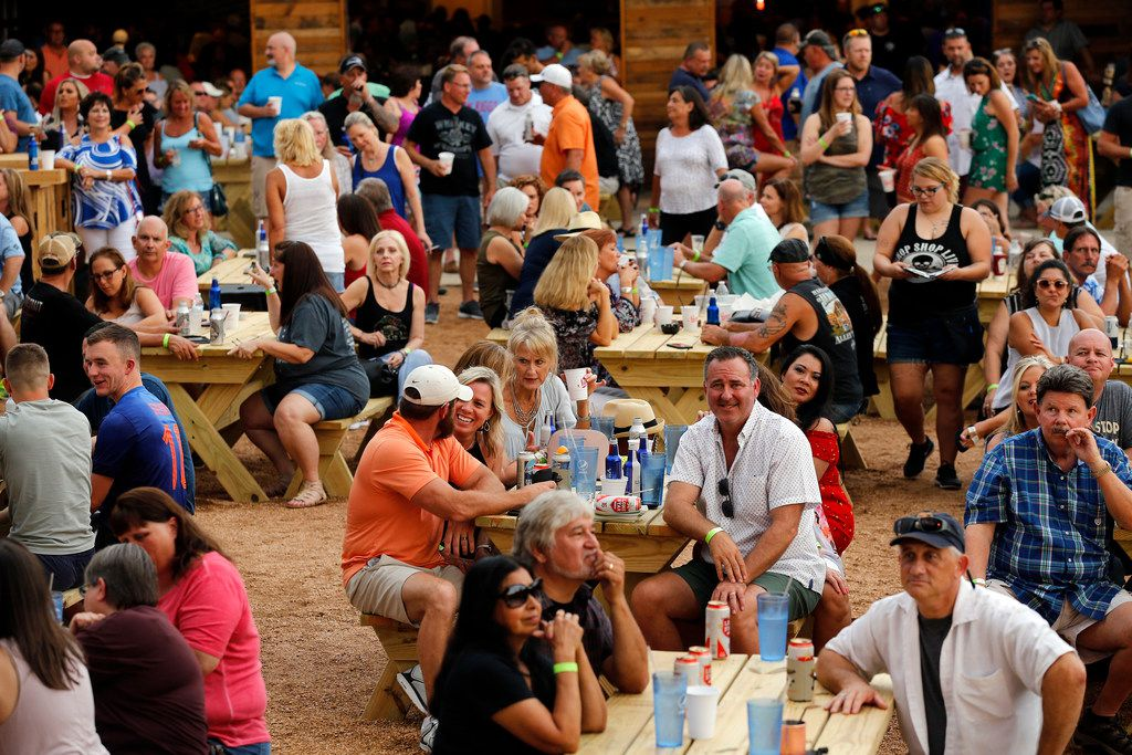 People gathered on picnic tables for drinks and conversation during opening night at ChopShop Live in Roanoke, Texas, Friday, July 6, 2018. (Tom Fox/The Dallas Morning News)