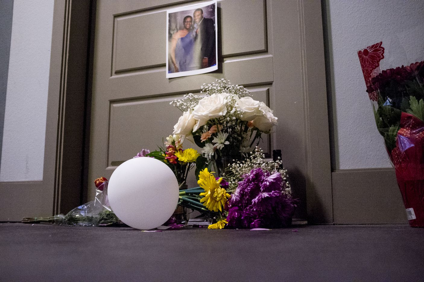 Flowers are placed at the front door apartment of Botham Jean on Monday, Sept. 10, 2018 in Dallas. Jean was shot Thursday by off-duty Dallas police officer Amber Guyger, who says she mistook his apartment for hers.