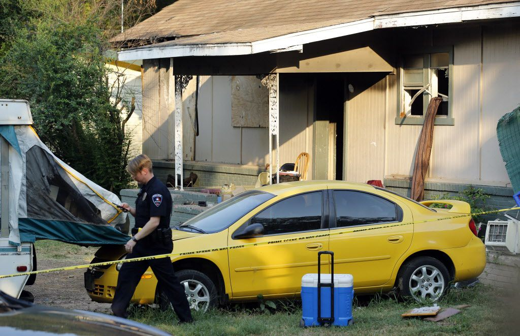 Un oficial de la polícia de Arlington camina cerca de la casa donde fueron encontrados dos cuerpos cerca del AT&T Stadium/ Tom Fox / DMN