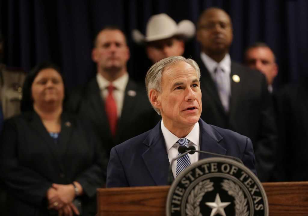 Surrounded by leadership of different law enforcement agencies, Texas Gov. Greg Abbott speaks during a new conference on April 10 in Houston.