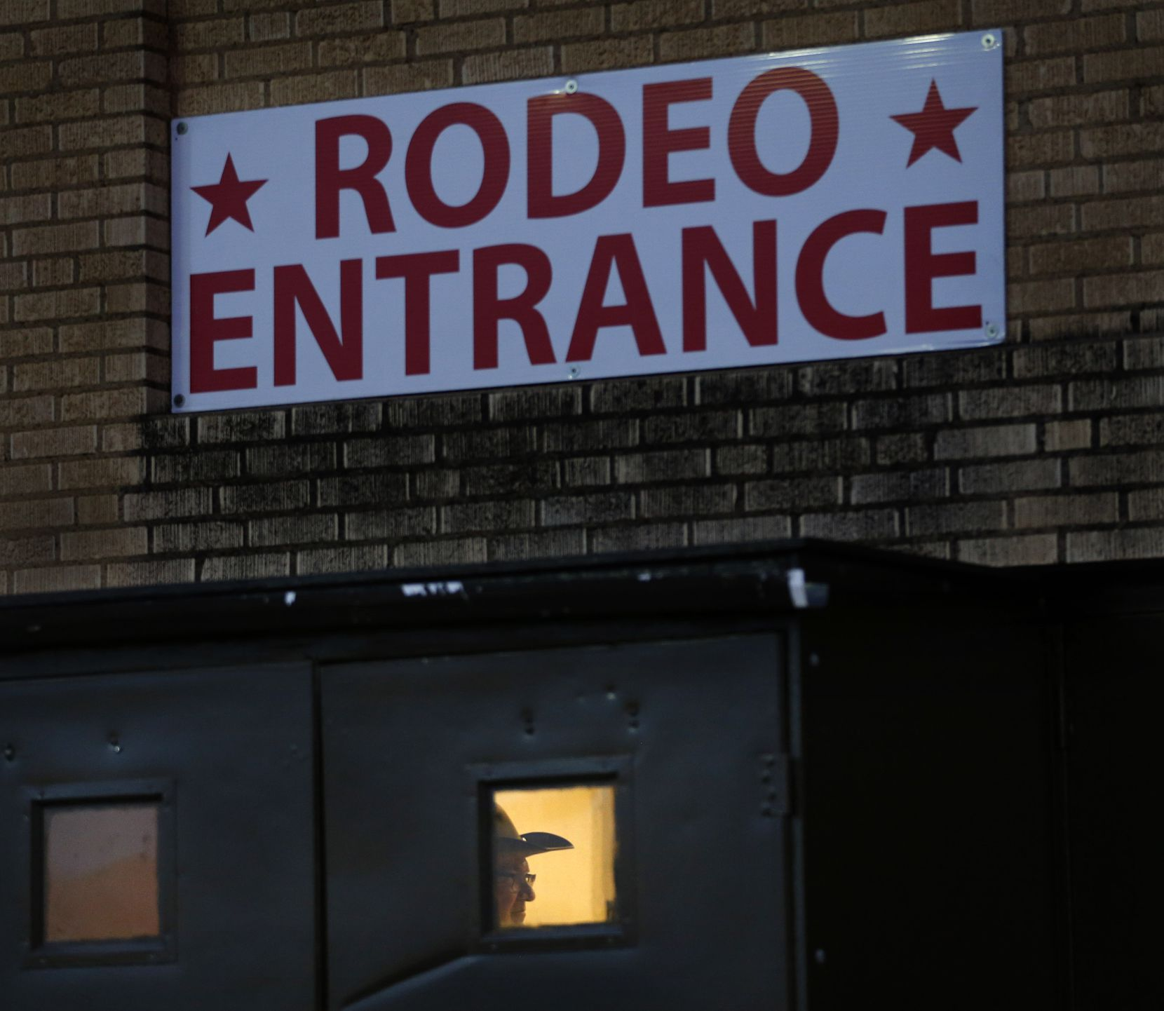 An usher is seen through the rodeo entrance doors of Will Rogers Memorial Coliseum at the Fort Worth Stock Show and Rodeo in Fort Worth, Wednesday, January 30, 2019.