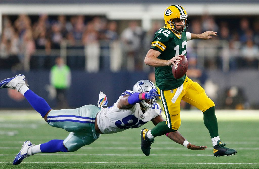Green Bay Packers quarterback Aaron Rodgers (12) shakes Dallas Cowboys defensive tackle David Irving (95)  as he rushes for 18 yards for a first down on a third down play in the last minute of play in the fourth quarter at AT&T Stadium in Arlington on Sunday, October 8, 2017. Green Bay Packers defeated the Dallas Cowboys 35-31. (Vernon Bryant/The Dallas Morning News)