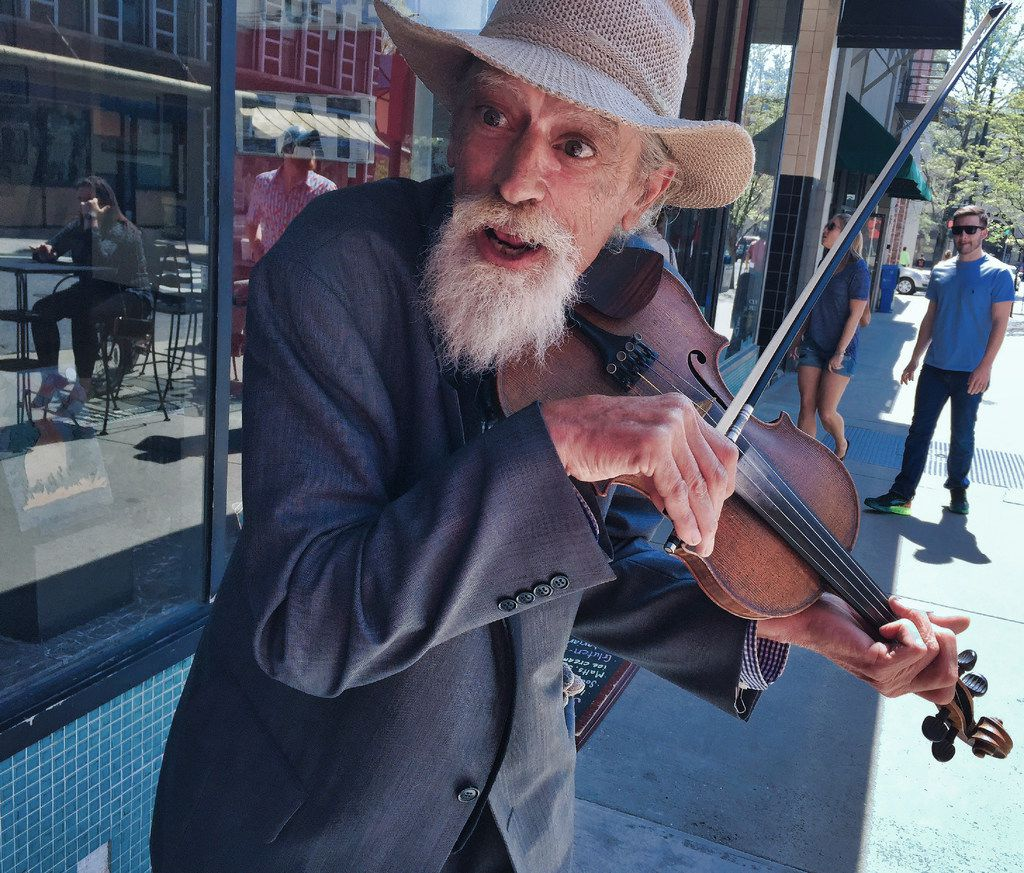 This musician, who goes by the name  Mikey, fiddles and plays authentic Appalachian tunes on the streets of Asheville.
