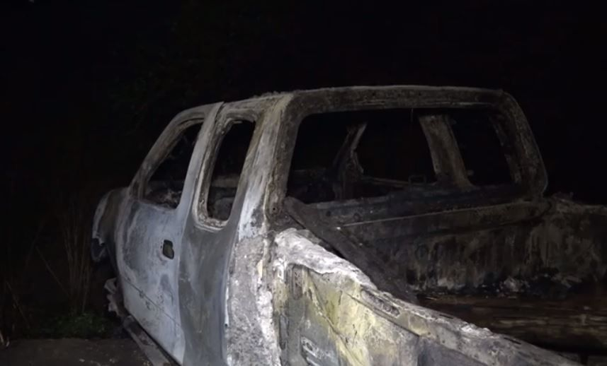 A charred pickup sits in a wooded area in Fort Worth after it caught fire Monday night. The driver was found injured a few feet away.