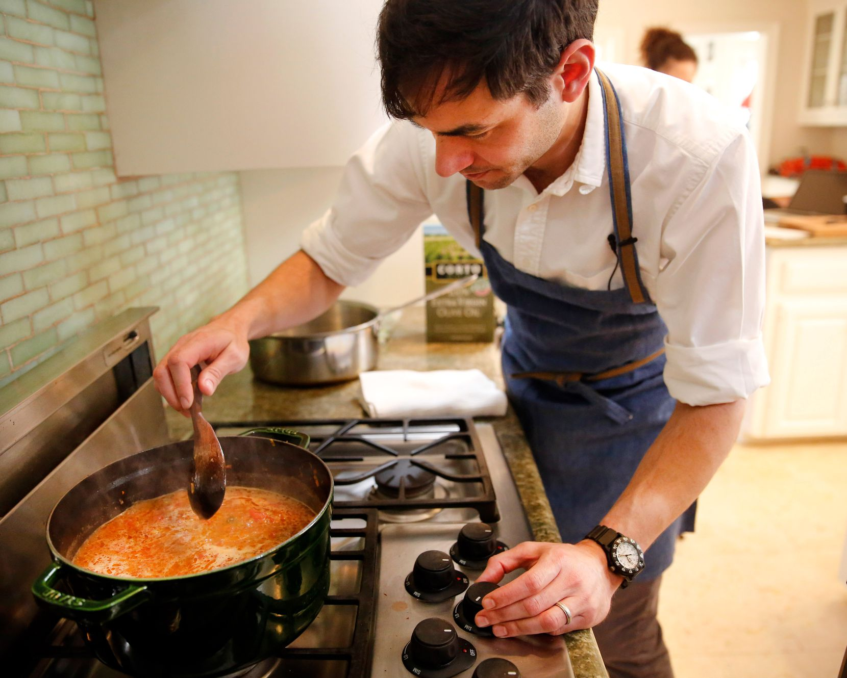 Restaurant owner and chef Julian Barsotti stirs bolognese sauce for the elaborate, multi-layered Italian dish known as a timpano at his Highland Park home. (Tom Fox/The Dallas Morning News)