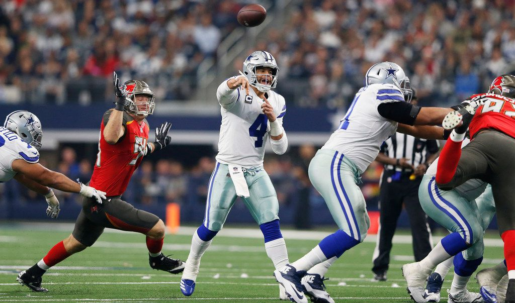 FILE - Cowboys quarterback Dak Prescott (4) attempts a pass as Tampa Bay Buccaneers defensive end Carl Nassib (94) closes in on him during the second half of a game at AT&T Stadium in Arlington on Sunday, Dec. 23, 2018. (Vernon Bryant/The Dallas Morning News)