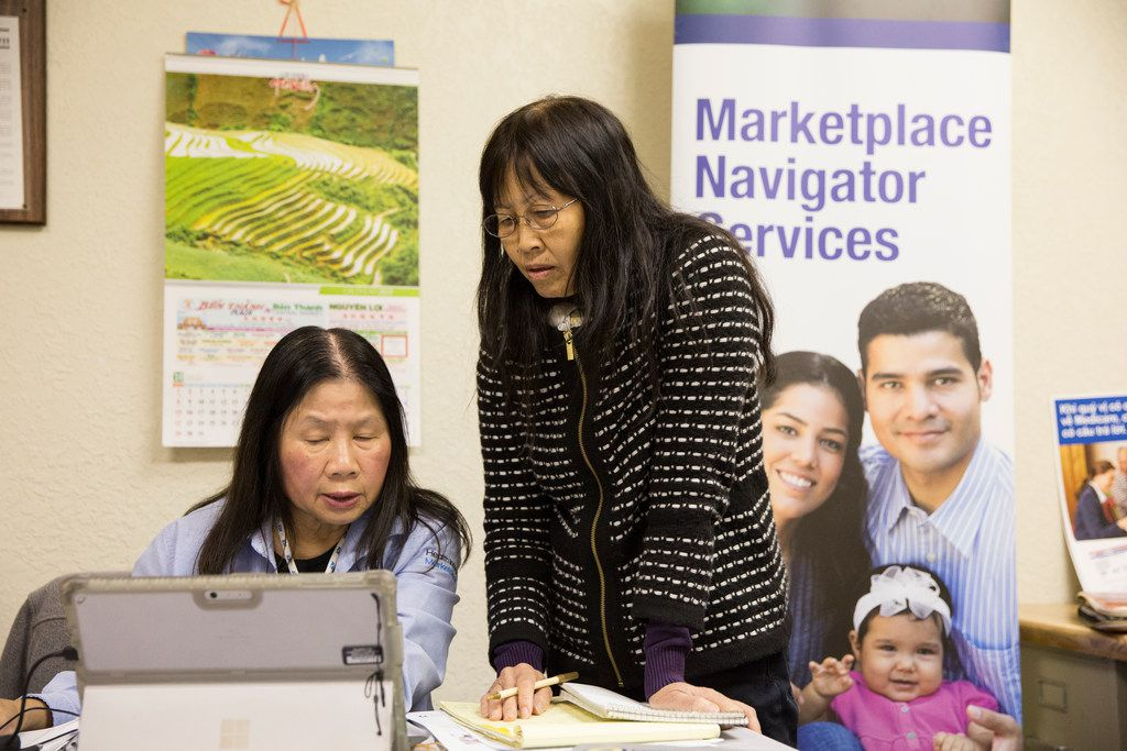 Lisa Pham (left), a Vietnamese-speaking health insurance marketplace navigator, speaks with her client, Mua Thi Nguyen, at the Vietnamese community center in Pantego.