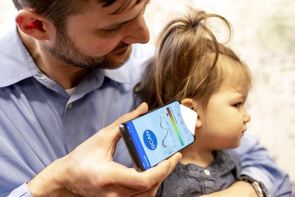 En esta imagen difundida por la Universidad de Washington en mayo de 2019, el doctor Randall Bly utiliza una app de un teléfono celular y un cono de papel para dirigir el sonido y revisar si su hija sufre de alguna infección auditiva, en la facultad de medicina de la Universidad de Washington en Seattle. (Dennis Wise/University of Washington via AP)