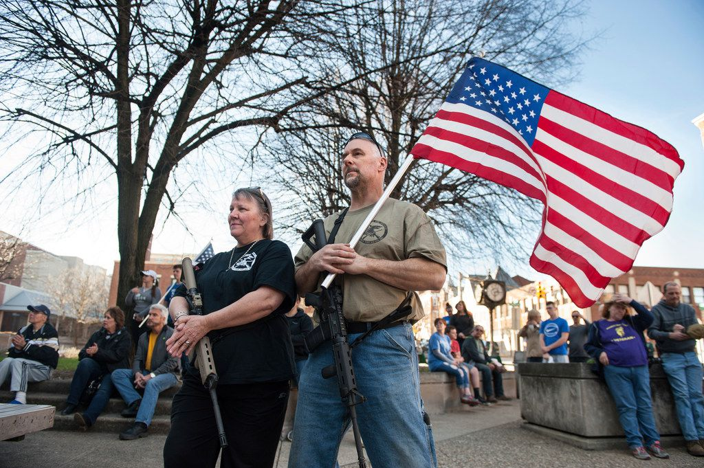 National Rifle Association instructor Marilyn Boulet, left, and her husband, Bill Perkins, of Gibsonia, rest their hands on their guns while gathering with other supporters of the Second Amendment at a pro-gun rally, Sunday, April 22, 2018, outside of the Westmoreland County Courthouse in Greensburg, Pa.