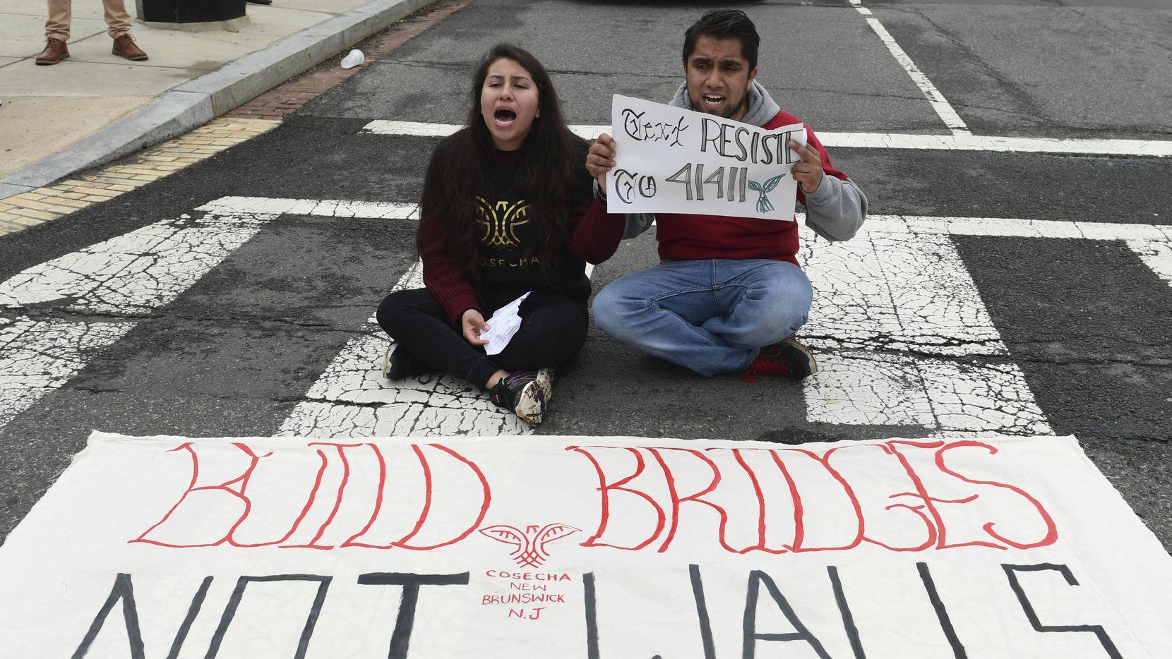 Dos personas no identificadas protestaron frente al Congreso el jueves, pidiendo una reforma migratoria que incluya alivio a los dreamers.(AP)