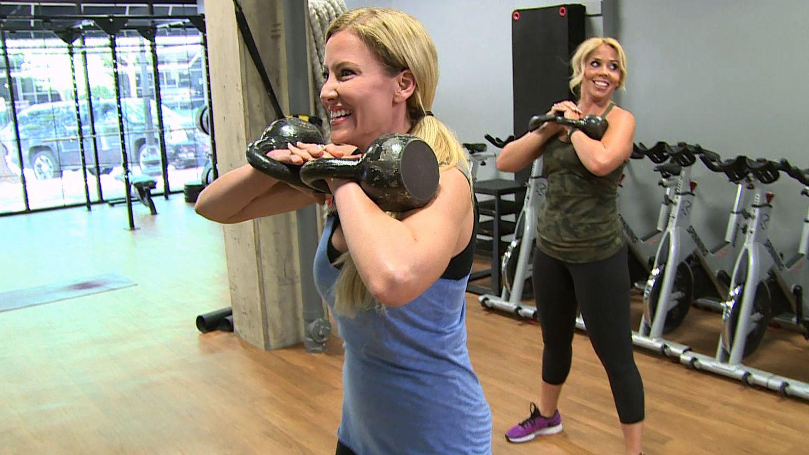 Stephanie Hollman, left, teaches writer Kimber Westphall how to do squats holding kettlebells.