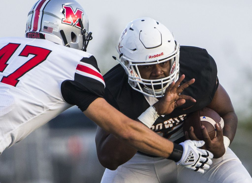 Arlington Bowie running back Marsaillus Sims (32) breaks a tackle by Flower Mound Marcus defensive lineman Connor Cronin (47) during the first quarter of a high school football game between Flower Mound Marcus and Arlington Bowie on Thursday, August 29, 2019 at Wilemon Field in Arlington. (Ashley Landis/The Dallas Morning News)