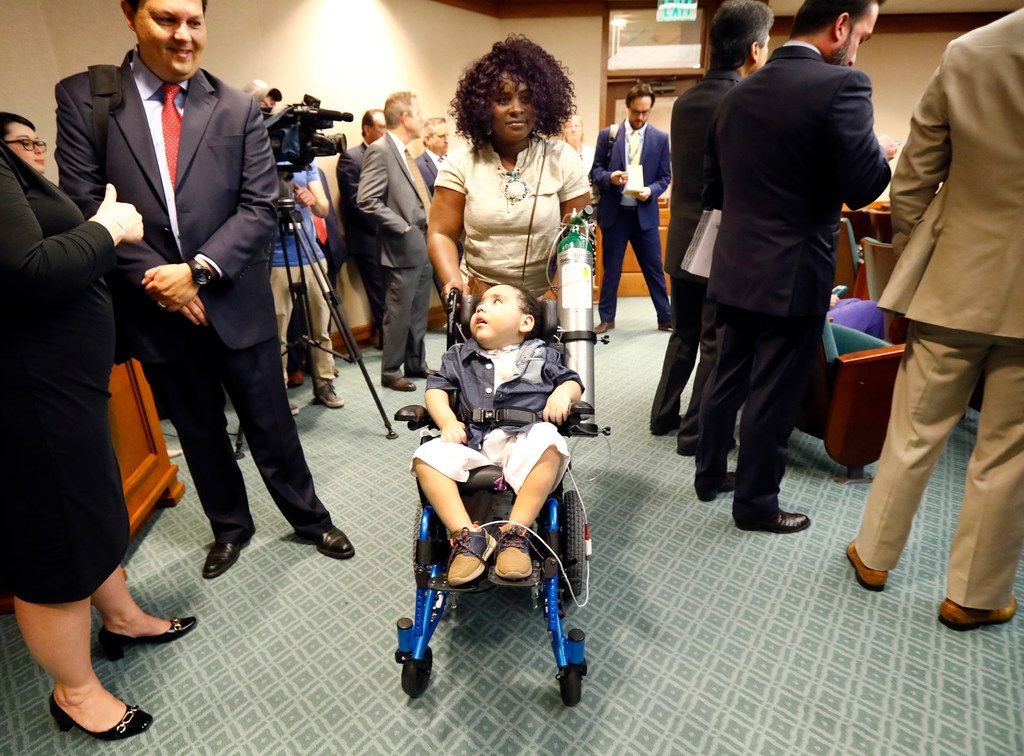Linda Badawo of Mesquite, Texas pushes her 3 yr-old son D'ashon Morris into a House Committee on Human Services meeting  at the State Capitol in Austin, Wednesday, June 20, 2018.