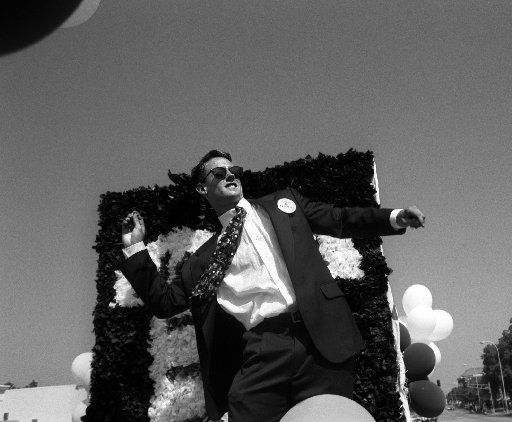 Brian Clark strikes a Heisman-like pose as he prepares to launch some candy to parade-goers along Hillcrest Avenue during the SMU Homecoming parade on Saturday, October 1, 1994.