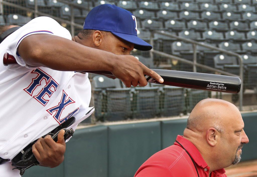 Texas third baseman Adrian Beltre tries to distract a video interview by tapping DMN baseball writer Evan Grant on the head with a bat at photo day during Texas Rangers baseball spring training in Surprise, AZ  on Tuesday, February 25, 2014.  (Louis DeLuca/Dallas Morning News)