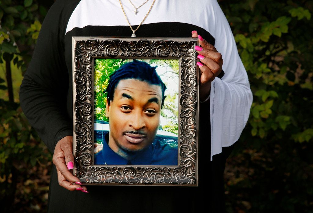 Sherley Woods, the mother of O'Shae Terry, holds a photo of her son at her home in Forest Hills.